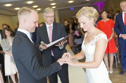 Die Braut steckt ihrem Bräutigam den Ring an den Finger