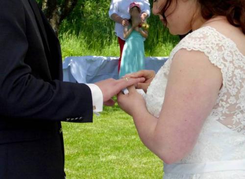 Der Bräutigam bekommt den Ring  von seiner Braut an die Hand gesteckt